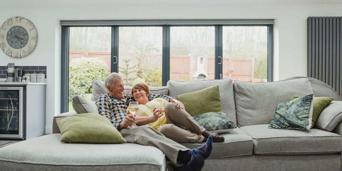 Retired couple enjowing a drink on the sofa