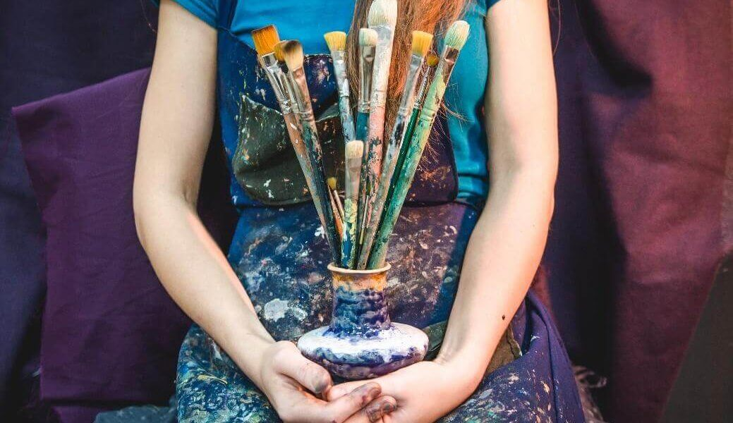 Artist covered in paint holding brushes